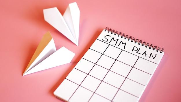 Koncepcja marketingu w mediach społecznościowych - plan smm w notatniku na różowym tle