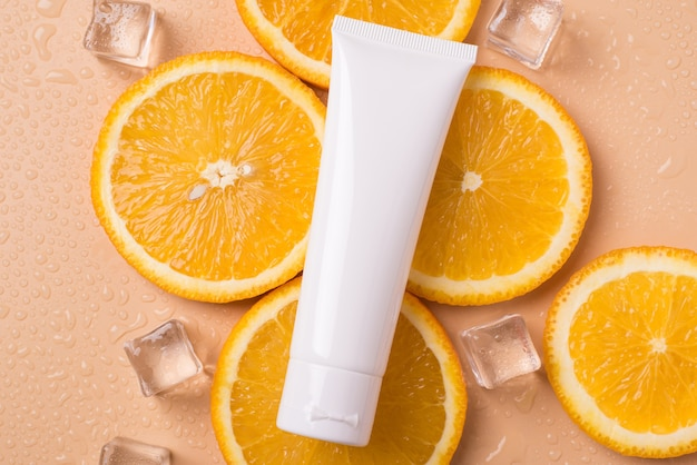 Koncepcja marki lato sezonu spa. u góry, nad głową, zdjęcie płaskie z rurką z kremem leżącą na pomarańczowych kostkach lodu owocowego na beżowej powierzchni