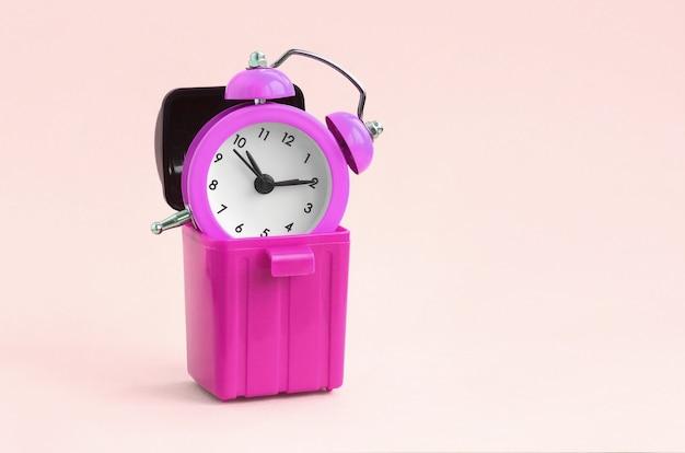 Koncepcja marnowania czasu. budzik w koszu na śmieci