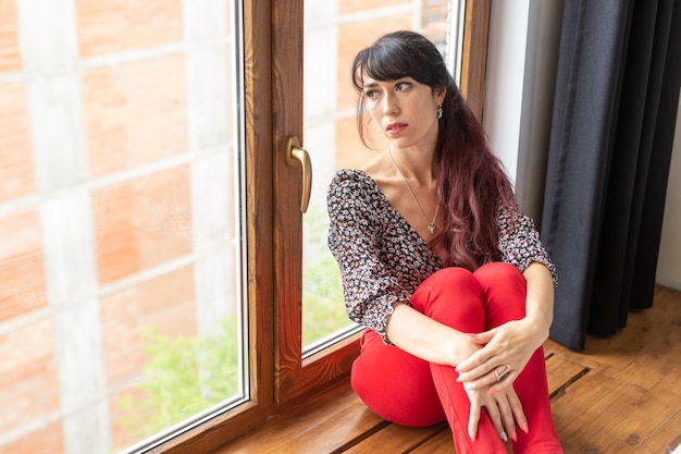 Koncepcja marzeń, zamyślenia i samotności - młoda kaukaska kobieta siedzi w swoim salonie i wygląda przez duże okno.