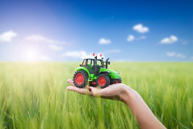 Koncepcja maszyn rolniczych i rolnik posiadający plastikową zabawkę ciągnika w polu.