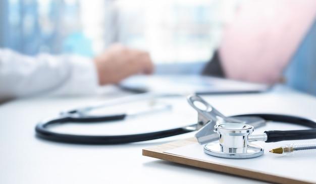 Koncepcja medycyny online. stetoskop i clipboard na stanowisku pracy lekarzy w tle, lekarz przeprowadza konsultację online z pacjentem za pomocą laptopa