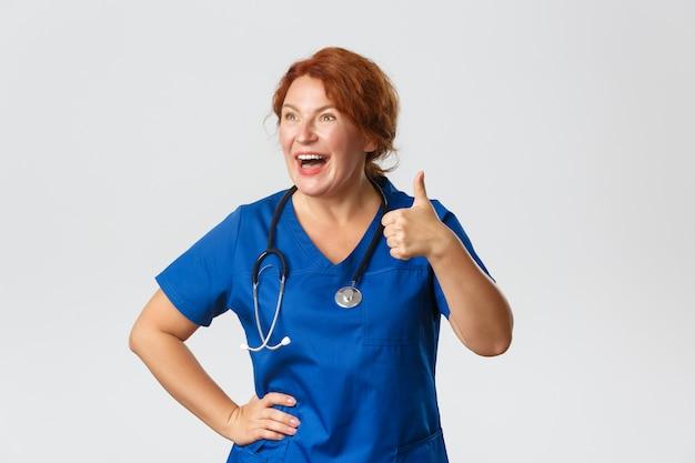 Koncepcja medycyny, opieki zdrowotnej i koronawirusa. podekscytowana i pod wrażeniem śmiejąca się, szczęśliwa ruda lekarka, pracownik medyczny pokazujący kciuki do góry i patrząc w lewo na coś dobrego, polecam.