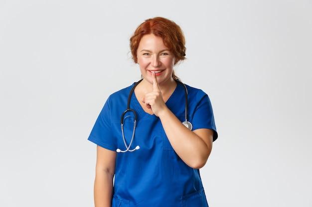 Koncepcja medycyny, opieki zdrowotnej i koronawirusa. szczęśliwa uśmiechnięta lekarka, pielęgniarka prosząca o zachowanie tajemnicy, uciszenie, przyciśnięcie palcem do ust i uciszenie, mówienie o ciszy, przygotowana niespodzianka, szare tło.
