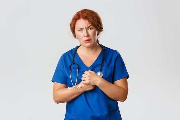 Koncepcja medycyny, opieki zdrowotnej i koronawirusa. współczująca rudowłosa pielęgniarka, lekarz w fartuchu patrzy z politowaniem, współczuje pacjentowi, stoi zaniepokojona szarym tłem.