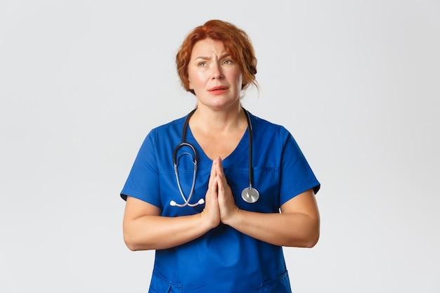 Koncepcja medycyny, opieki zdrowotnej i koronawirusa. zmartwiona i pełna nadziei rudowłosa pracownica medyczna z nadzieją na koniec pandemii, modląca się lub błagająca ze złożonymi rękami.