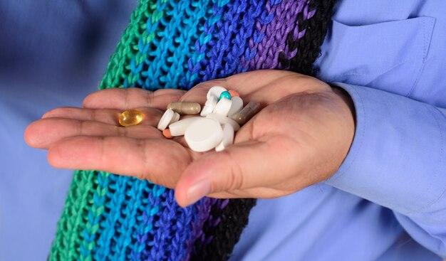 Koncepcja medyczna ręka człowieka trzyma różne pigułki różne pigułki przepisane przez medycynę lekarską