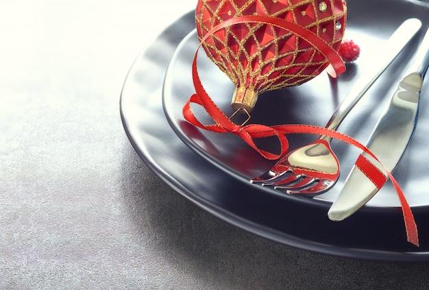 Koncepcja menu świątecznego z czarnymi talerzami i sztućcami ozdobionymi wstążkami i bombkami