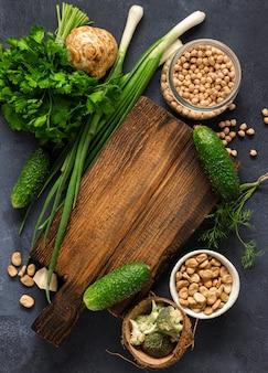 Koncepcja menu wegańskie. drewniana nieociosana tnąca deska z składnikami dla gotować weganinu jedzenie na ciemnego tła odgórnym widoku