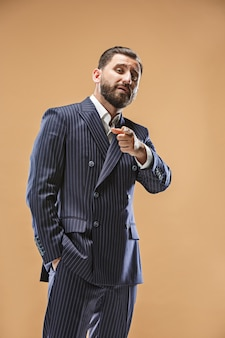 Koncepcja męskiej urody. portret młodego mężczyzny modnego ze stylową fryzurą na sobie modny garnitur pozowanie