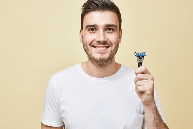 Koncepcja męskości, piękna i pielęgnacji skóry. portret przystojnego młodego mężczyzny z włosiem z szerokim uśmiechem trzymającego kij do golenia, zamierzającego golić brodę rano przed pracą