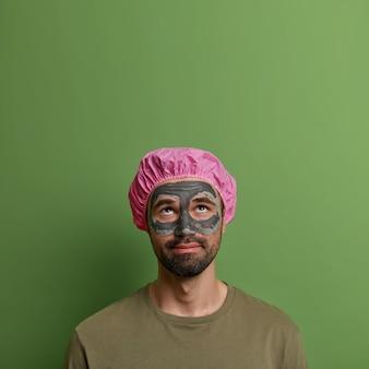 Koncepcja mężczyzn, kosmetologii, higieny i urody. uważny, poważny mężczyzna skoncentrowany powyżej, nakłada glinianą maskę na twarz w celu odmłodzenia, ma gruby zarost, nosi czapkę prysznicową, patrzy na pustą przestrzeń w górę