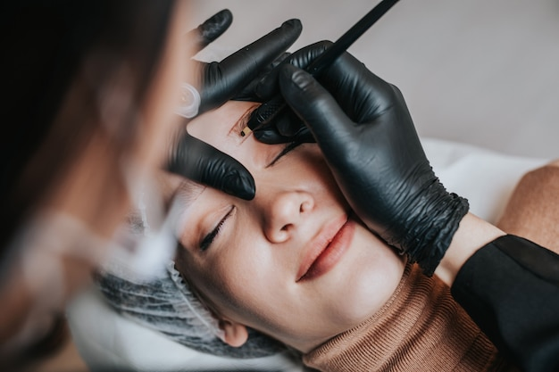 Koncepcja microbladingu brwi, procedura makijażu permanentnego brwi. ekspert kosmetyczny ma na sobie maskę ochronną i maskę ochronną z powodu pandemii koronawirusa.