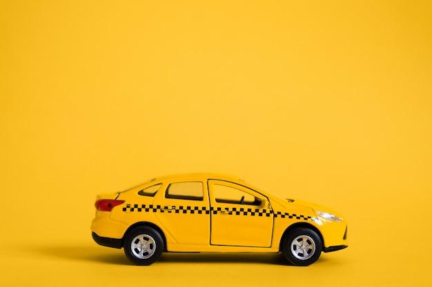 Koncepcja miejskiej taksówki i usługi dostawy. zabawka żółty model samochodu taxi. skopiuj miejsce na tekst, baner. aplikacja mobilna zamówić taksówkę online.