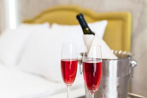 Koncepcja miesiąca miodowego. wiadro szampana przy łóżku w pokoju hotelowym