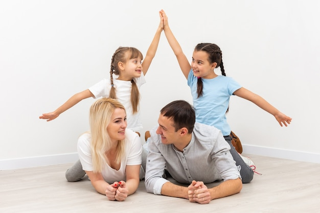 Koncepcja mieszkania młodej rodziny. matka tata i dzieci w nowym domu z dachem