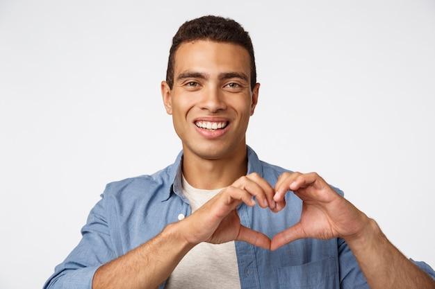 Koncepcja miłości, cherity i przywiązania. powabny młody brazylijski męski mężczyzna pokazuje serce znaka i ono uśmiecha się szczęśliwy