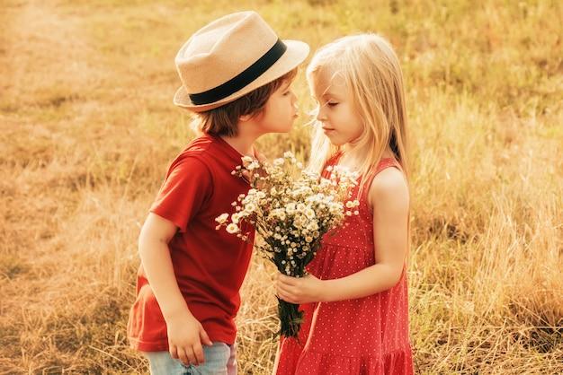 Koncepcja miłości dla dzieci. dzieci mają pocałunek w jesiennym polu.