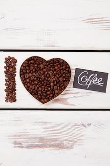 Koncepcja miłości do kawy. płaskie świeckie ziarna kawy ułożone w kształcie serca i słowo i. białe drewno na powierzchni.