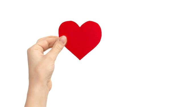Koncepcja miłości dziecka. ręka trzyma czerwone serce na białym tle na białym tle. skopiuj zdjęcie miejsca