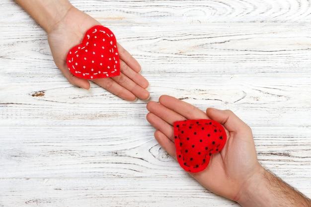 Koncepcja miłości: dziewczyna gospodarstwa i dając czerwone serce jej chłopaka rękę na białym tle