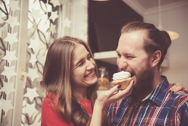 Koncepcja miłości i przyjaźni. młoda piękna i szczęśliwa kaukaska para ściska podczas gdy mieć dobry czas wpólnie w domu. przystojny mężczyzna z grubą stylową brodą obejmując swoją dziewczynę