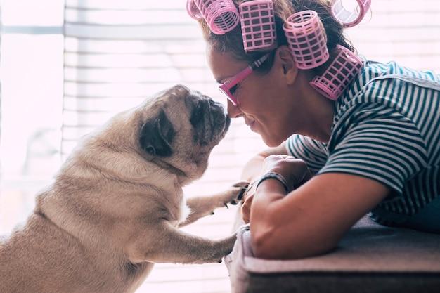 Koncepcja miłości i przyjaźni z ładną kaukaską młodą kobietą położyła się na kanapie w domu i uroczym uroczym mopsem całującym ją w nos - lokówki na głowie, aby przygotować się do aktywności