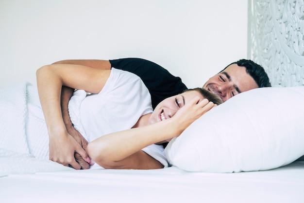 Koncepcja miłości i związku z młodą parą śpiącą w białej sypialni i łóżku razem ze szczęściem i uśmiechem