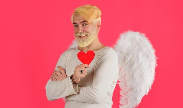 Koncepcja miłości, przystojny anioł z czerwonym sercem, brodaty mężczyzna z anielskimi skrzydłami, walentynki.