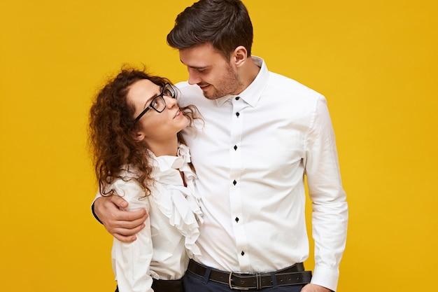 Koncepcja miłości, randek, romansu i relacji. wysoki przystojny facet obejmujący swoją piękną dziewczynę, która patrzy na niego z pasją. śliczna romantyczna para pozowanie na białym tle, przytulanie, przytulanie