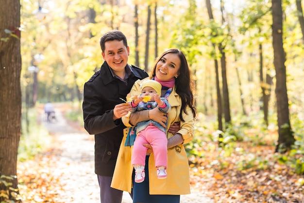 Koncepcja miłości, rodzicielstwa, rodziny, sezonu i ludzi - uśmiechnięta para z dzieckiem w jesiennym parku