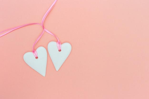Koncepcja miłości romantycznej. dwa białe serca i różowa wstążka na różowym papierze w pastelowym kolorze. serca powiązane. walentynki minimalistyczny styl.