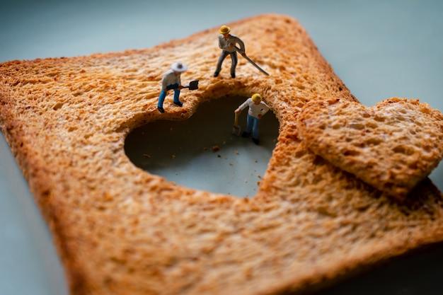 Koncepcja miłości. smutny związek. grupa robotników miniaturowe serce mocujące