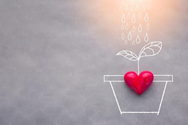 Koncepcja miłości z czerwonym sercem obiektu i rysunek drzewa podlewania