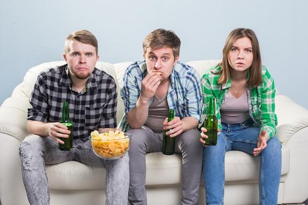 Koncepcja mistrzostw świata w piłce nożnej - młodzi przyjaciele piją piwo i kibicują piłce nożnej