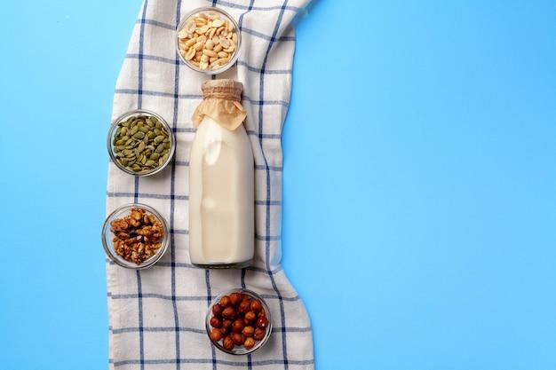 Koncepcja mleka roślinnego z butelką mleka i miski z widokiem z góry ziaren i orzechów