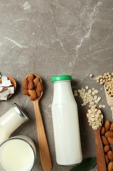 Koncepcja mleka wegańskiego na szarym tle z teksturą, widok z góry