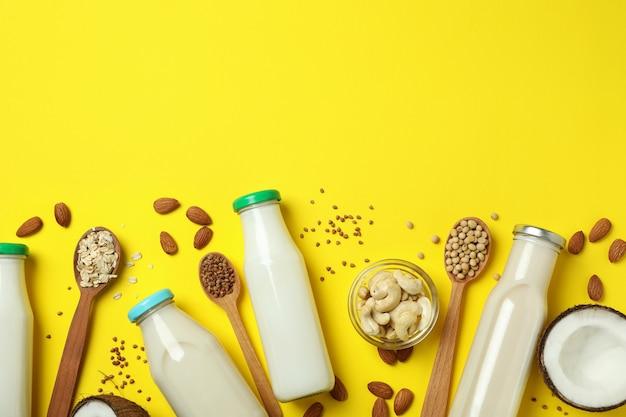 Koncepcja mleka wegańskiego na żółtym tle, widok z góry
