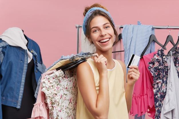 Koncepcja młodości, mody, stylu i szczęścia. urocza młoda kobieta rasy kaukaskiej posiadająca certyfikat, korzystająca z zakupów w butikach odzieżowych, wybierając letnie ubrania, czując się szczęśliwa i podekscytowana