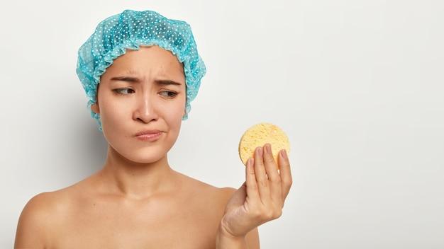 Koncepcja młodości, rozpieszczania, czyszczenia i pielęgnacji skóry. niezadowolona młoda chinka patrzy nieszczęśliwie na gąbkę kosmetyczną, usuwa makijaż, nosi niebieskie ochronne nakrycie głowy