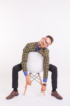 Koncepcja moda i ludzie - przystojny brodaty pewnie mężczyzna siedzi na krześle na białym tle.