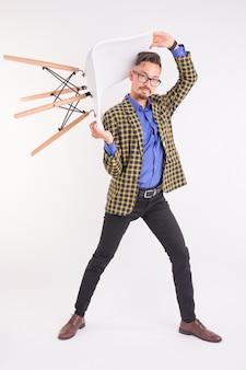 Koncepcja moda i ludzie - przystojny mężczyzna w okularach skręcanie z krzesłem.