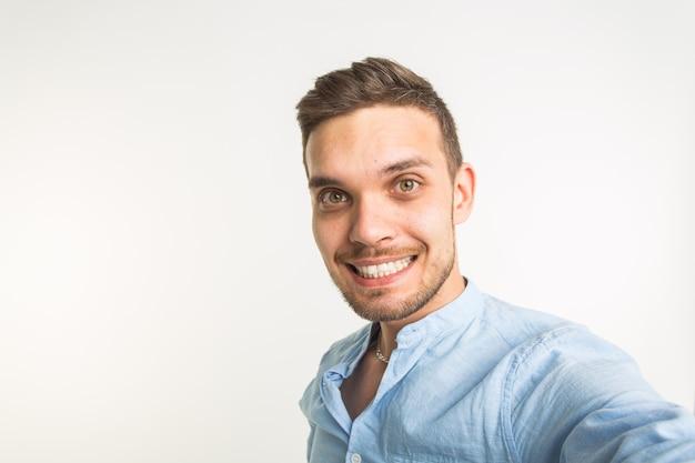 Koncepcja moda i ludzie - przystojny mężczyzna zrobić zdjęcie selfie i uśmiechać się na białej ścianie