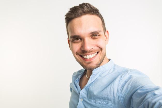 Koncepcja moda i ludzie - przystojny mężczyzna zrobić zdjęcie selfie i uśmiechać się na białej ścianie.