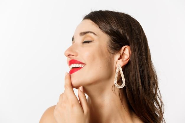 Koncepcja moda i uroda. ujęcie w głowę zmysłowej brunetki kobiety z kolczykami i czerwoną szminką, uśmiechającej się skuszonej i dotykającej wargi, stojącej na białym tle.