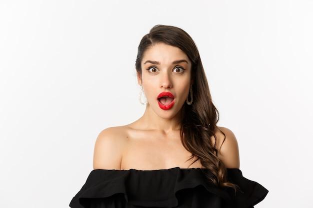 Koncepcja moda i uroda. zbliżenie: brunetka kobieta w czarnej sukni otwarte usta zaskoczony, patrząc z podziwem na aparat, białe tło.