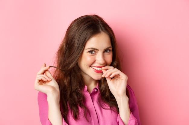 Koncepcja moda i uroda. zbliżenie młodej kobiety flirtującej, śmiejącej się kokieteryjnie i bawiącej się kosmykiem włosów, uśmiechającej się do ciebie, stojącej nad różową ścianą.