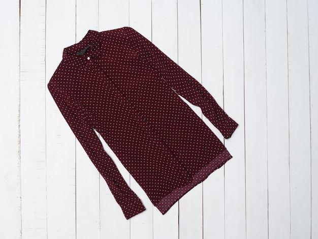 Koncepcja moda ubrania. burgundowa koszula na białym drewnianym tle. widok z góry