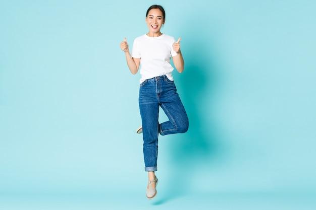 Koncepcja moda, uroda i styl życia. optymistyczna ładna azjatka w swobodnym stroju, ciesząca się zakupami, skacząca ze szczęścia i podniecenia, pokazująca kciuki do góry na jasnoniebieskiej ścianie.