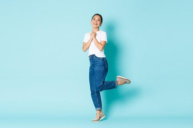 Koncepcja moda, uroda i styl życia. romantyczna i rozmarzona piękna azjatka w swobodnym stroju, wyglądająca uroczo, spleciona w dłonie pozuje na jasnoniebieskiej ścianie.